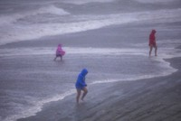 People walk on the beach in Garden City, S.C., as Isaias approached the Carolinas on Aug. 3, 2020. (Jason Lee/The Sun News via AP)