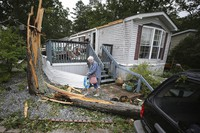 Ellen Mallen, who lives in a mobile home court, carefully leaves her home after a suspected tornado spawned by Isaias struck Marmora, N.J., on Aug 4, 2020. (David Maialetti/The Philadelphia Inquirer via AP)