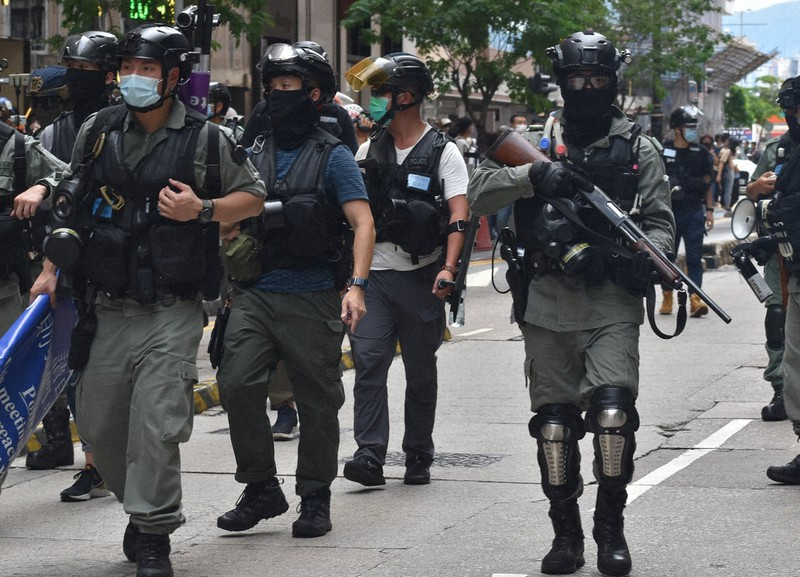銃を手にデモ隊の制圧に向かう機動隊員ら=香港・銅鑼湾で2020年7月1日午後2時24分、福岡静哉撮影