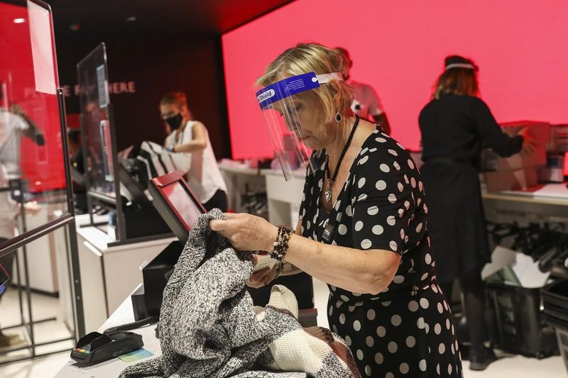フェイスガードをつけて作業する百貨店の従業員(ロンドン)(Bloomberg)