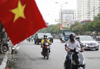People wearing face masks ride mopeds in Hanoi, Vietnam, on Aug. 6, 2020. (AP Photo/Hau Dinh)