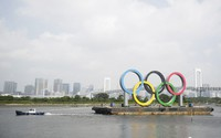 A tugboat moves a symbol installed for the Olympic and Paralympic Games Tokyo 2020 on a barge moved away from its usual spot off the Odaiba Marine Park in Tokyo, on Aug. 6, 2020. (AP Photo/Hiro Komae)