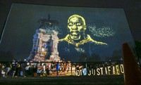An image of George Floyd is projected on a screen in front of the statue of Confederate General Robert E. Lee on Monument Avenue on July 28, 2020, in Richmond, Va. (AP Photo/Steve Helber)