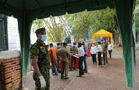 A Sri Lankan government soldier stands guard at the entrance to a ballot counting center as workers show their identity to police officers, a day after voting for general elections in Colombo, Sri Lanka, on Aug. 6, 2020. (AP Photo/Eranga Jayawardena)