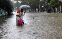 People wade through a water-logged street during heavy rain in Mumbai, India, on Aug. 5, 2020. (AP Photo/Rajanish Kakade)