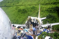 Officials stand on the debris of the Air India Express flight that skidded off a runway while landing at the airport in Kozhikode, Kerala state, India, on Aug. 8, 2020. (AP Photo/C.K.Thanseer)