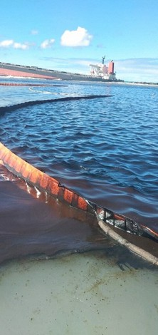 This photo taken and provided by Georges de La Tremoille of Mu Press shows a containment boom collecting oil leaking from the MV Wakashio, a bulk carrier ship that recently ran aground off the southeast coast of Mauritius, Friday, Aug. 7, 2020.(Georges de La Tremoille/MU Press via AP)