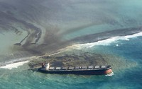 This photo taken and provided by Eric Villars shows oil leaking from the MV Wakashio, a bulk carrier ship that recently ran aground off the southeast coast of Mauritius, on Aug. 7, 2020. (Eric Villars via AP)