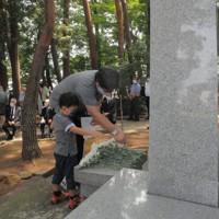 原爆死没者慰霊碑に献花する参列者たち=宇都宮市西川田町の県総合運動公園で