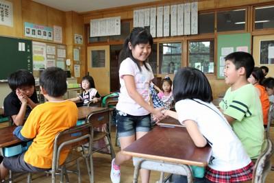 2学期が始まり、避難先から戻ったクラスメート(手前)を歓迎し握手する児童たち=福島県相馬市の中村第二小学校で、2011年8月23日午前10時36分、武市公孝撮影