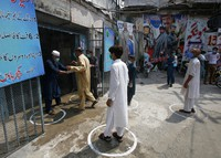 People wear face masks and keep social distancing as they enter a cinema following an ease in restrictions that had been imposed to help control the coronavirus, in Peshawar, Pakistan, on Aug. 10, 2020. (AP Photo/Muhammad Sajjad)