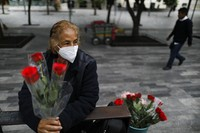 Wearing a mask to curb the spread of the new coronavirus, Martha Gonzalez Reyes, 76, sells roses outside Metro Hidalgo in central Mexico City, on Aug. 10, 2020. (AP Photo/Rebecca Blackwell)