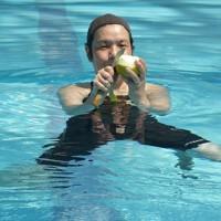 立ち泳ぎをしながら梨をむく踏水会の会員=熊本市南区で2020年8月12日、城島勇人撮影