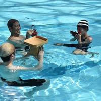 立ち泳ぎをしながら酒を酌み交わすパフォーマンスを披露する踏水会の会員=熊本市南区で2020年8月12日、城島勇人撮影