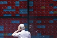 A man looks at an electronic stock board showing Japan's Nikkei 225 index at a securities firm in Tokyo on Aug. 12, 2020. (AP Photo/Eugene Hoshiko)