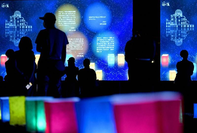 「オンライン灯籠流し」のイベントで、スクリーンに映された平和を願うメッセージを見つめる人たち=広島市中区で2020年8月6日午後8時1分、山田尚弘撮影