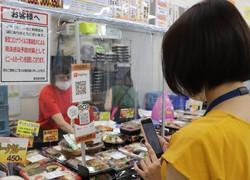 QRコード決済で弁当を購入する女性。JPQRは乱立するサービスの切り札となるか=東京・霞が関の中央合同庁舎2号館で2020年6月18日午前11時7分、後藤豪撮影