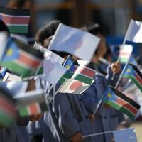 地元幼稚園の交流会で南スーダンと日本の国旗を振る園児たち=前橋市で2020年2月13日、久保玲撮影