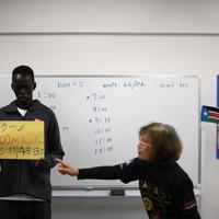 日本語学校の授業で自己ベストと目標タイムを話すアクーン・ジョセフ選手(左)=前橋市で2019年12月18日、久保玲撮影