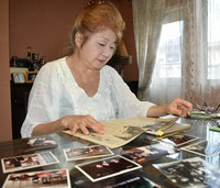Shigeko Masunaga, who lost her father in a deadly Japan Airlines flight crash in 1985, is seen looking at magazines, pictures and other material from the time of the accident, in this photo taken in Kamakura, Kanagawa Prefecture, on Aug. 3, 2020. (Mainichi/Atsuko Suzuki)