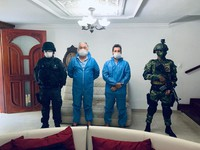 In this photo released by Colombia's Prosecutor's Press Office, a police officer and a soldier flank Mark Grennon, second from left, and his son Joseph Grennon, during a raid in Santa Marta, Colombia, on Aug. 11, 2020. (Colombia's Prosecutor's Press Office via AP)
