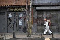 A city worker sprays disinfectant on shuttered storefronts in the Catia neighborhood of Caracas, Venezuela, on Aug. 8, 2020, amid the new coronavirus pandemic. (AP Photo/Matias Delacroix)