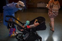 Spanish NGO Open Arms volunteer, Julia Martin, 38, plays with 4-month old Biel, as his father takes a COVID-19 PCR test, at Vilafranca del Penedes in the Barcelona province of Spain, on Aug. 11, 2020. (AP Photo/Emilio Morenatti)