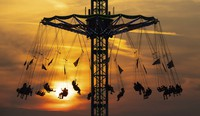 Numerous people ride a chain carousel in the Olympic Park in Munich, Germany, during sunset on Aug. 12, 2020. (Sven Hoppe/dpa via AP)