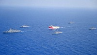 In this photo provided by the Turkish Defense Ministry, Turkey's research vessel, Oruc Reis, in red and white, is surrounded by Turkish navy vessels as it was heading in the west of Antalya on the Mediterranean, Turkey, on Aug 10, 2020. (Turkish Defense Ministry via AP)