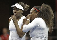 In this Feb. 11, 2018 file photo, U.S.A.'s Venus Williams, left, and Serena Williams, right, talk between points in their doubles match against Netherlands' Leslie Herkhove and Demi Schuurs in the first round of Fed Cup tennis competition in Asheville, North Carolina. (AP Photo/Chuck Burton)