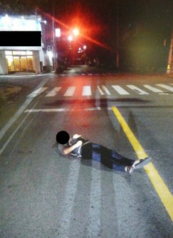 A person is seen sleeping on the road in this image provided by Okinawa Prefectural Police's Yaeyama Police Station.