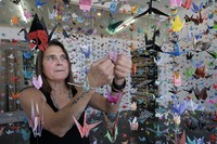 Artist Karla Funderburk, owner of Matter Studio Gallery, adjusts one of the thousands of origami cranes hanging during an exhibit honoring the victims of COVID-19, on Aug. 11, 2020, in Los Angeles. (AP Photo/Richard Vogel)