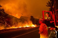 A firefighter watches as a helicopter drops water on the Lake Hughes fire in Angeles National Forest on Aug. 12, 2020, north of Santa Clarita, Calif. (AP Photo/Ringo H.W. Chiu)
