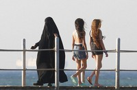 In this July 26, 2019 file photo, holiday makers walk at al Sokhna beach in Suez, Egypt. The burkini, a swimsuit worn by conservative Muslims to cover the entire body, is scorned in many upper class Egyptian circles, which see it and the headscarf as lower class. (AP Photo/Amr Nabil)