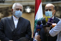 Lebanese Foreign Minister Charbel Wehbe, left, speaks during a joint press conference with his Iranian counterpart Mohammad Javad Zarif, outside the Lebanese foreign ministry damaged by last week's explosion that hits the seaport of Beirut, Lebanon, on Aug. 14, 2020. (AP Photo/Hussein Malla)