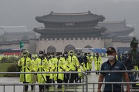Police officers wearing face masks patrol around the Gyeongbok Palace, one of South Korea's well-known landmarks, in Seoul, South Korea, on Aug. 15, 2020. (AP Photo/Ahn Young-joon)