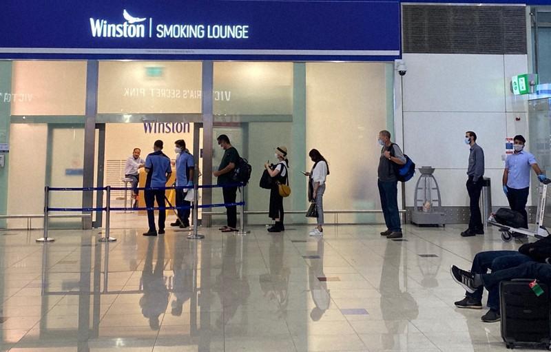 新型コロナ感染拡大を受けて、人数制限のある喫煙室に並ぶ人たち=ドバイ国際空港で2020年8月16日、真野森作撮影
