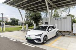 太陽光発電パネルの下で、充電している電気自動車。普及に弾みがつくかも?(Bloomberg)