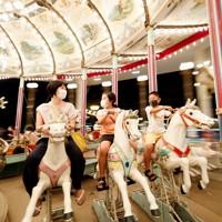 閉園するとしまえんで世代を超えて愛されてきた世界最古級の木製メリーゴーラウンド「カルーセルエルドラド」に乗る親子連れ=東京都練馬区で2020年8月2日、吉田航太撮影