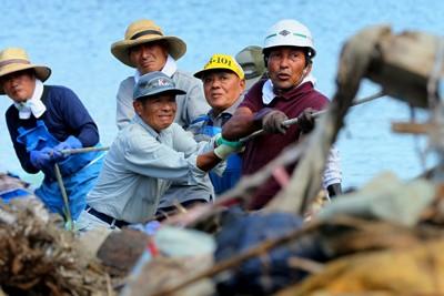 長面浦の岸辺に打ち上げられたがれきをロープで引っ張り撤去する県漁協河北町支所の組合員ら=宮城県石巻市で2011年9月7日、森田剛史撮影