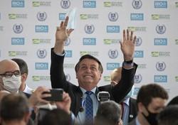 マスクを外し、手を挙げるブラジルのボルソナロ大統領=2020年8月14日、南東部リオデジャネイロで、AP
