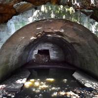 断崖に掘った横穴に造られた津和瀬砲台。トンネル内に砲座があり、中央奥の開口部から洞窟につながる=福岡県宗像市で2020年8月16日、森園道子撮影