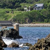 陸軍が設置した潮位を計測するための水尺(中央左の柱)。奥は沖津宮遥拝所=福岡県宗像市で2020年8月16日、森園道子撮影
