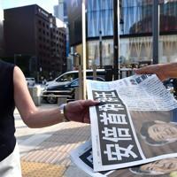 安倍首相辞任を知らせる号外を受け取る人たち=東京都中央区で2020年8月28日午後4時27分、西夏生撮影