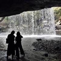 鍋ケ滝の裏側で水のカーテンを楽しむ人たち=熊本県小国町で2020年8月24日、田鍋公也撮影