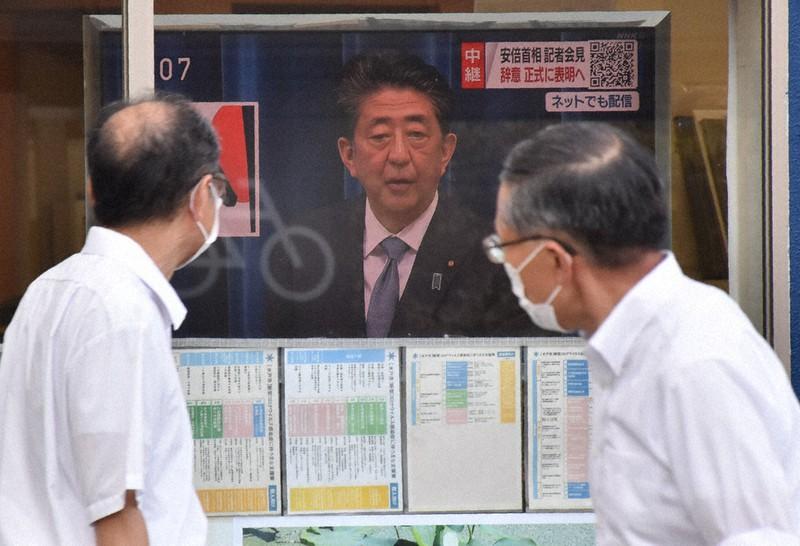 店頭のテレビで安倍首相の辞任会見を見る人たち=水戸市三の丸で、川島一輝撮影