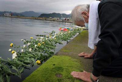 震災から半年となる9月11日、岩手県大槌町赤浜地区の合同供養祭後、参加者は菊の花を海に手向けた。最後に献花した男性は岸壁に膝と手をつき、深々と頭を下げた=岩手県大槌町で2011年9月11日、和田大典撮影