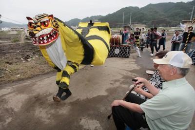 鵜住神社の祭礼で、津波の被害を受けた町の中に虎が舞い、訪れた人たちの笑顔をさそった=岩手県釜石市鵜住居で2011年9月13日午後4時31分、岩下幸一郎撮影