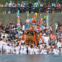 4年ぶりに復活した大杉神社の海上渡御で、大勢の見物人が見守る中、修復された神輿を担いで海に入り潮ごりする若い衆=岩手県山田町で2014年9月15日、鬼山親芳撮影