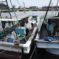 台風10号による暴風や高波などに備え、漁船同士をロープで固定する漁業者たち=福岡県行橋市蓑島で
